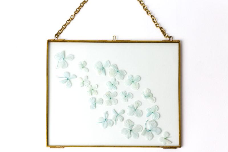 messing bild aus glas mit echten hortensien blüten in blau als dekoration für zuhause